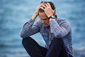 Akupunktur mod stress og angst Valby, Frederiksberg, København, mand holder sig for hovedet ved vandet