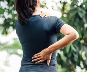 Akupunktur rygsmerter Valby, Frederiksberg, København, dame tager sig til ryggen